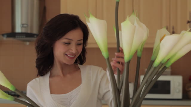 MS Woman arranging Calla lilies in kitchen / China