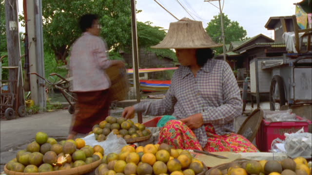Woman arranging fruit display on her market stall Available in HD.