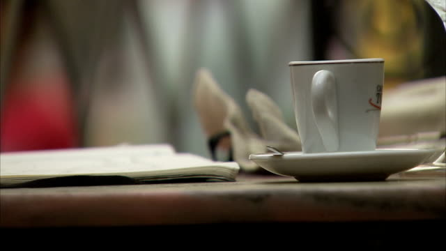 A woman at an outdoor cafe places a teacup on a saucer. Available in HD.