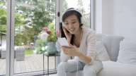 Woman at home listening music with headphones