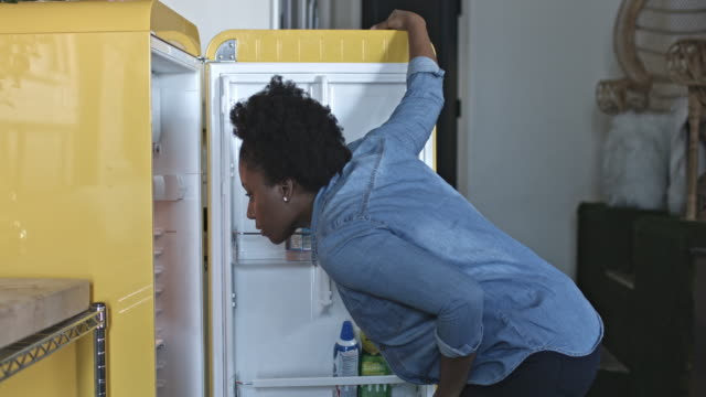 Woman at home opening the fridge to pick an apple
