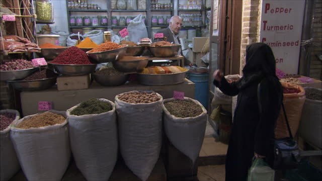 MS Woman at market stall with dried food and spices, Grand Bazaar, Isfahan, Iran
