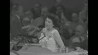 Woman at podium behind microphones chairman Joe Martin beside her bangs gavel / same woman wearing Harold Stassen button and Martin at podium / woman...
