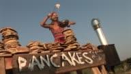 LA MS Woman at roadside pancake stand putting batter on stove/ Watermill, New York
