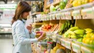 Frau im Supermarkt mit einer Einkaufsliste