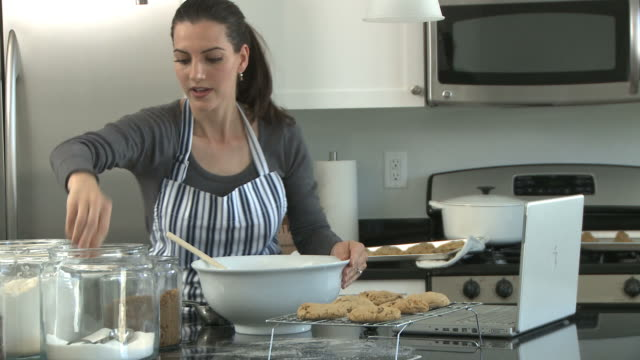 woman baking and using a laptop to follow a recipe online