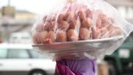 A woman balances a plate of eggs on her head in the city of Accra.