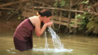 MS TS Woman bathing and washing in river /  Vang Vieng, Vientiane, Laos