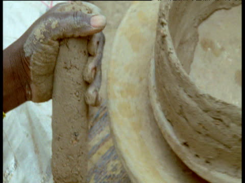 Woman begins to build up pot on wheel, Djenne