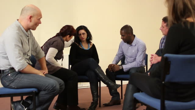 Woman being consoled in small group counselling therapy