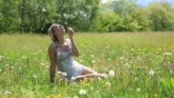 Woman blowing dandelion petals