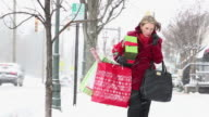 WS PAN Woman Blowing Nose in Snow, Holding Christmas Presents on City Street / Richmond, Virginia, United States