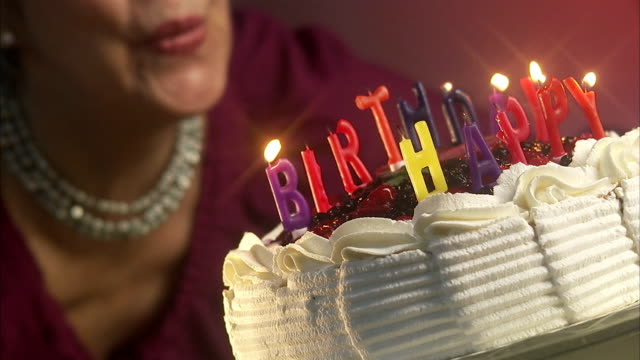 Woman blowing out the candles on a birthday cake, Sweden.