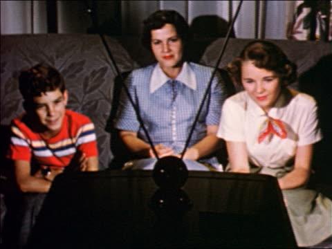 1950 woman, boy + teen girl sitting on sofa watching television / industrial / jump cut