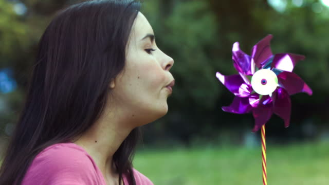 Woman breathing on a pinwheel in slow motion