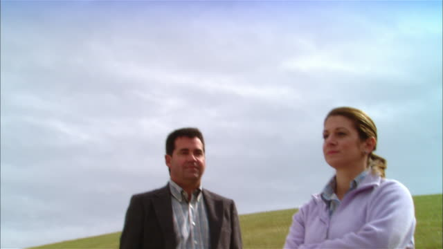 MS Woman + businessman standing in field near wind turbines on hill / Livermore, California, USA