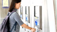 Woman buy the ticket by automatic ticket dispenser