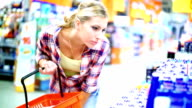 Woman buying cosmetic products in supermarket.