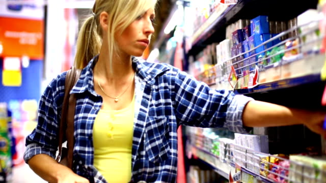 Woman buying in supermarket.