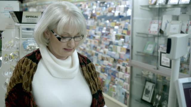 CU, Woman buying pills in pharmacy, Scotch Plains, New Jersey, USA