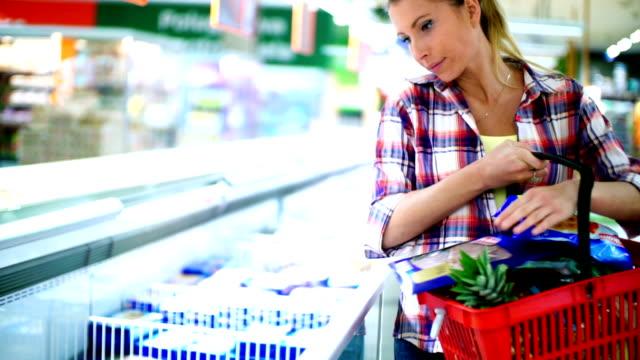 Vrouw wat bevroren voedsel in de supermarkt kopen.