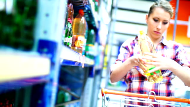 Woman buying water in supermarket.