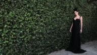 Woman by hedge wearing black evening gown