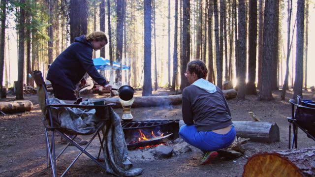 Woman Campers Tending to Campfire and Making Coffee