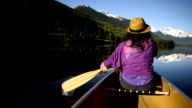 Woman canoeing on a pristine mountain lake