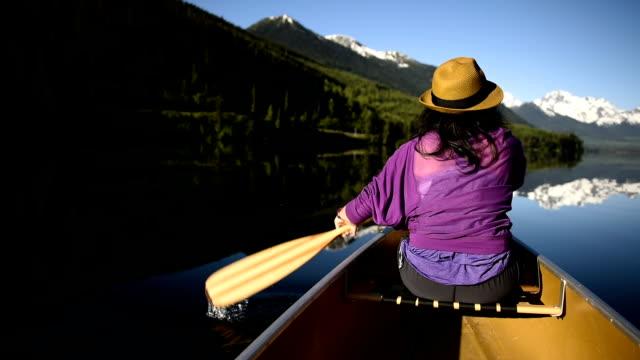 Woman canoeing on a pristine mountain lake