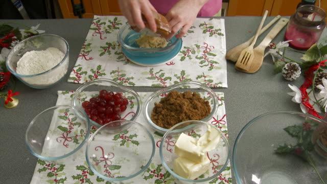 Woman Carefully Measures Chopped Almonds into a Glass Ramekin