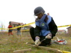 A woman carefully tests ground for buried mines following end of civil conflict in Kosovo 1999