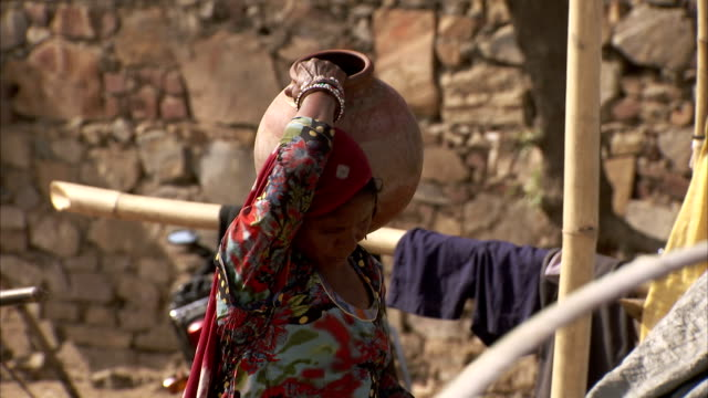 A woman carries a pot on her shoulder.