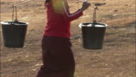 MS TS PAN ZO Woman carrying buckets of water, Laos
