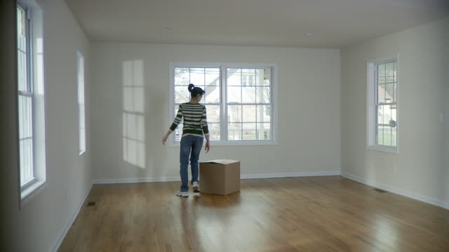 WS, Woman carrying cardboard box in empty room, Plainfield, New Jersey, USA