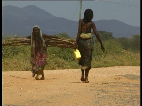 Woman carrying large bundle of sticks and woman carrying water container stop to speak on dusty road