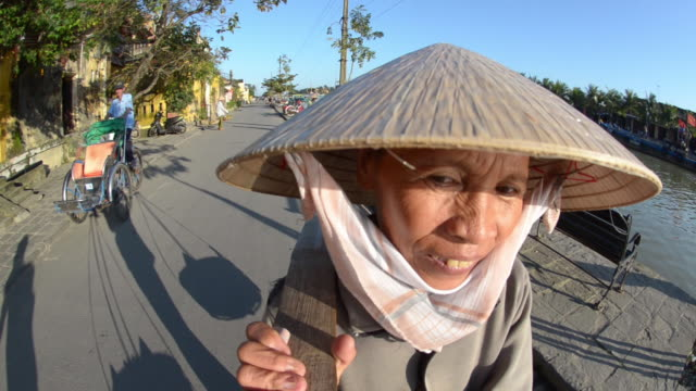 Woman carrying yoke baskets of fruit in street, Hoi An, Vietnam