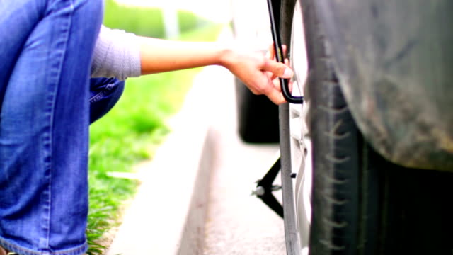 Woman changing flat tire on her car.