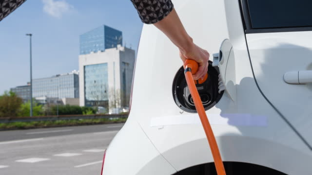 Woman charging electric car in the city
