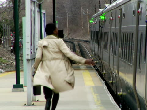 MS, Woman chasing for train on station platform, rear view, Chappaqua, New York State, USA