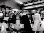 A woman chats to a salesman about televisions in an electrical goods shop 1957