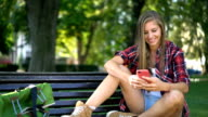 Woman chatting online on her phone in the park