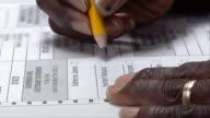 CU, ZI, Woman checking box next to name on ballot, Ypsilanti, Michigan, USA