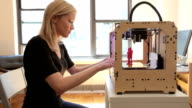 Woman checking print on open source 3D printer