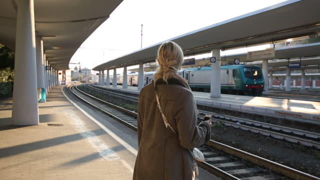 Woman checks phone at station platform, waiting for train