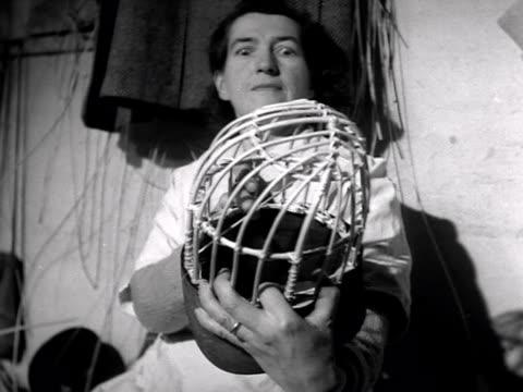 A woman checks the basket frame for a Grenadier Guards bearskin cap