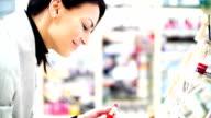 Woman choosing a lipstick at beauty store.
