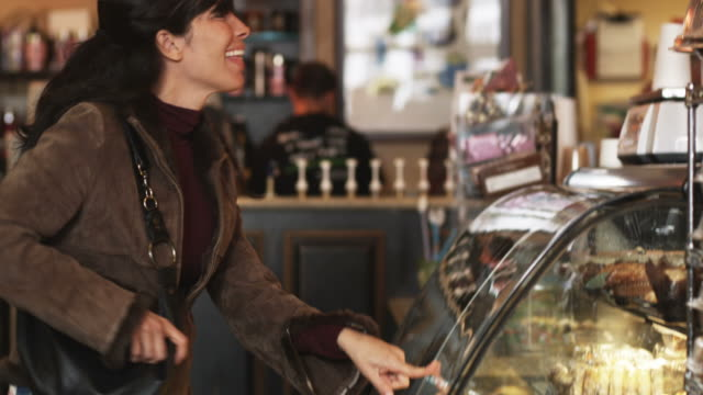 woman choosing and buying a baked good at a bakery