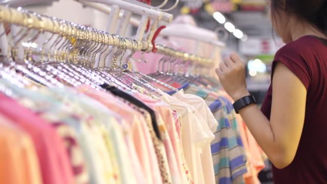Kvinna som du väljer kläder i gallerian