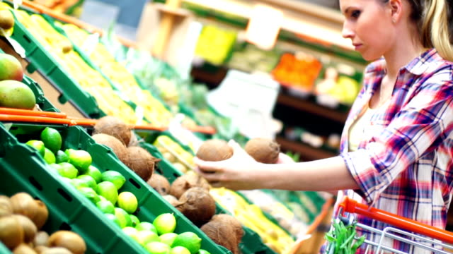Woman choosing fruit in supermarket.